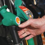 (FILES) This file photo taken on January 20, 2016 shows a customer reaching for an unleaded petrol nosel at a fuel pump outside a Royal Dutch Shell petrol station in Hook, near Basingstoke. Energy giant Royal Dutch Shell on May 25, 2016, said it was cutting at least another 2,200 jobs following its takeover of smaller rival BG Group and owing to low oil prices. / AFP / ADRIAN DENNIS