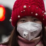 """BEIJING, CHINA - DECEMBER 08:  A Chinese woman wears a mask to protect against pollution as they wait to cross the street in heavy smog on December 8, 2015 in Beijing, China. The Beijing government issued a """"red alert"""" for the first time since new standards were introduced earlier this year as the city and many parts of northern China were shrouded in heavy pollution. Levels of PM 2.5, considered the most hazardous, crossed 400 units in Beijing, lower than last week, but still nearly 20 times the acceptable standard set by the World Health Organization. The governments of more than 190 countries are meeting in Paris to set targets on reducing carbon emissions in an attempt to forge a new global agreement on climate change.  (Photo by Kevin Frayer/Getty Images)"""
