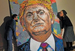 Ukranian artists Daria Marchenko and Daniel Green are seen with their portrait of US President Donald Trump, made of US pennies, nickels,and dimes, January 30, 2018 in New York. They leapt to fame in 2015 with a portrait of Vladimir Putin made up entirely of bullet shells gathered from the war zone in eastern Ukraine. Today, two Ukrainian artists are back with a portrait of Donald Trump, made up entirely of coins and poker chips. / AFP PHOTO / Don EMMERT / RESTRICTED TO EDITORIAL USE - MANDATORY MENTION OF THE ARTIST UPON PUBLICATION - TO ILLUSTRATE THE EVENT AS SPECIFIED IN THE CAPTION