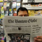 "Phillip Minias, 46, owner of Snax Express, reads the Boston Globe, August 15, 2018 in Boston, Massachusetts. - Branded ""enemy of the people"" by us President Donald Trump, the US news media is responding with a campaign aimed at countering the president's narrative and highlighting the importance of a free press. More than 200 news organizations are to participate in a coordinated campaign on August 16, 2018, with editorials about the importance of an independent media and a social media hashtag #EnemyOfNone. The move comes in response to a call by the Boston Globe amid a growing sense of unease that Trump's rhetoric is harmful to a free press and may even incite violence against journalists. (Photo by Joseph PREZIOSO / AFP)"